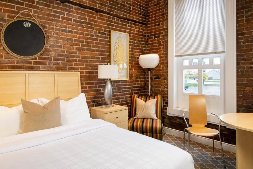 a queen bed with exposed brick walls in chardonnay suite