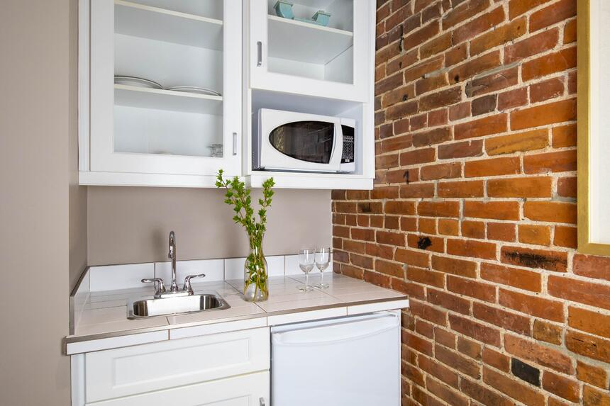 a kitchenette with a sink and microwave, exposed brick