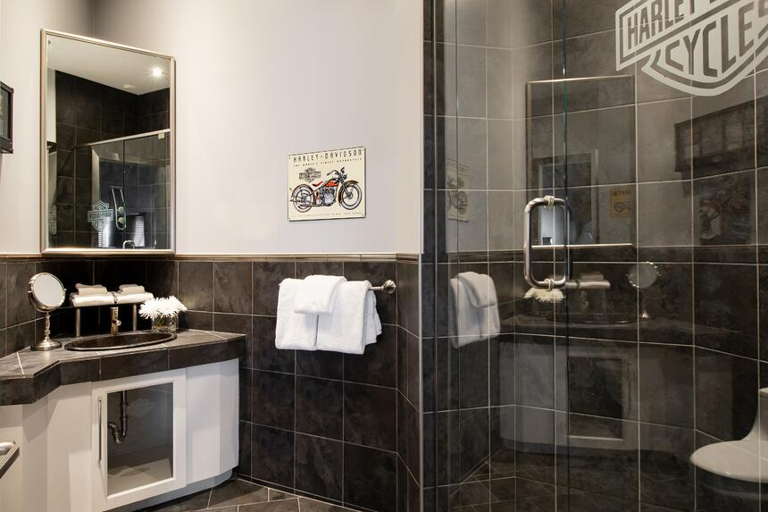 bathroom with harley davidson logo painted on dark tile in glass