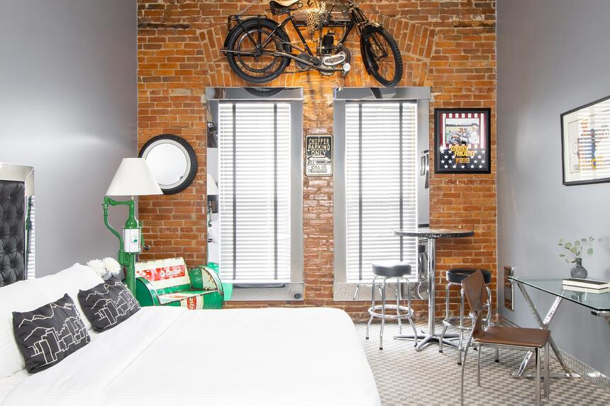 full view of easy rider room with bed and motor cycle hanging fr