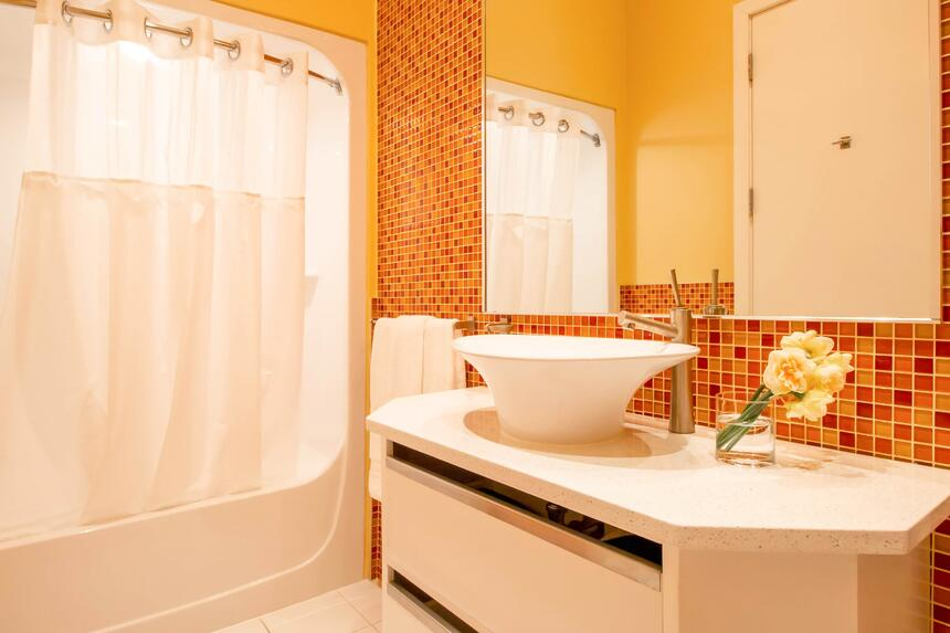 orange tile bathroom with raised white sink mirror