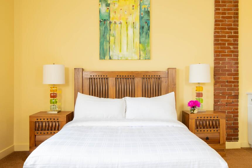 queen bed in mellow with blue and yellow original artwork