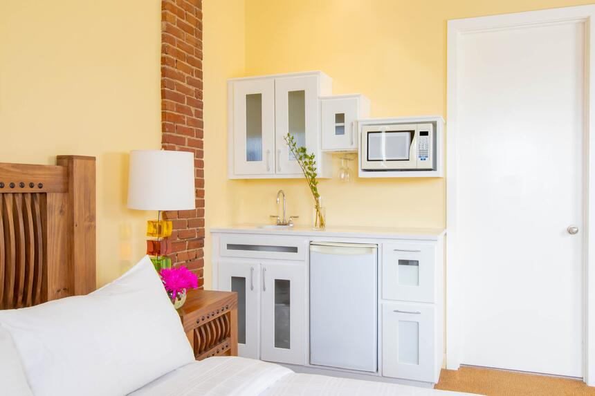 queen bed facing kitchenette with microwave and mini fridge