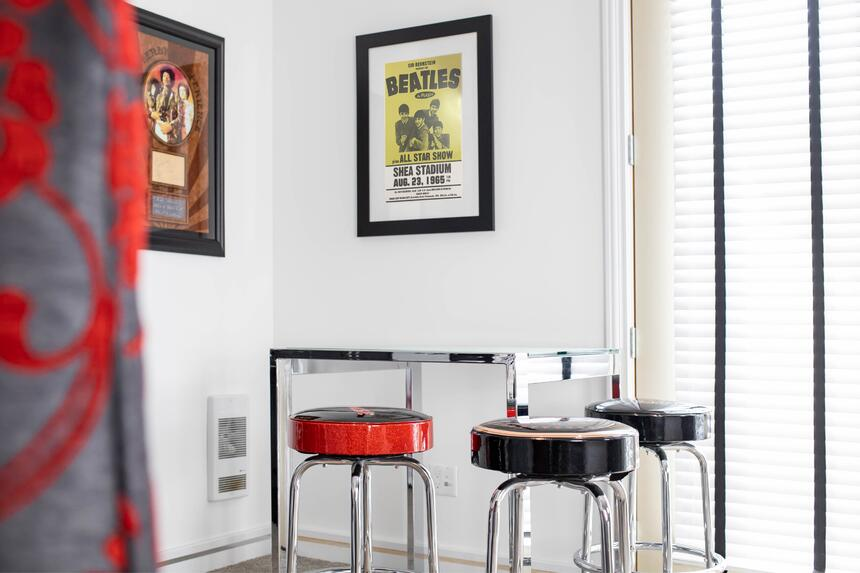 table with 4 stools, rock n roll themed, beatles poster