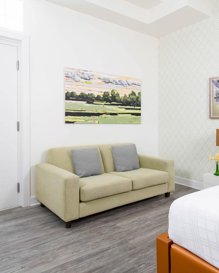 couch in spring fling suite 205 with artwork hanging above