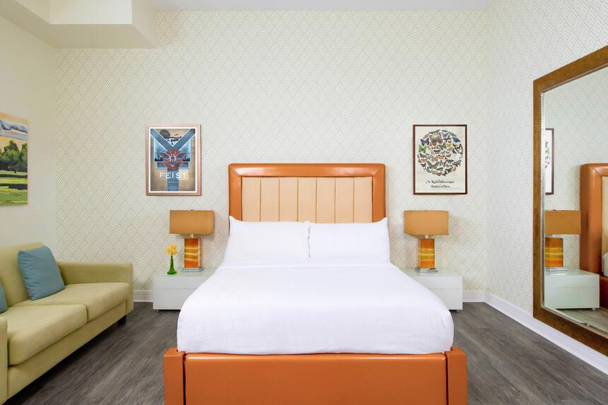 queen bed with orange leather bedframe and a large mirror and co