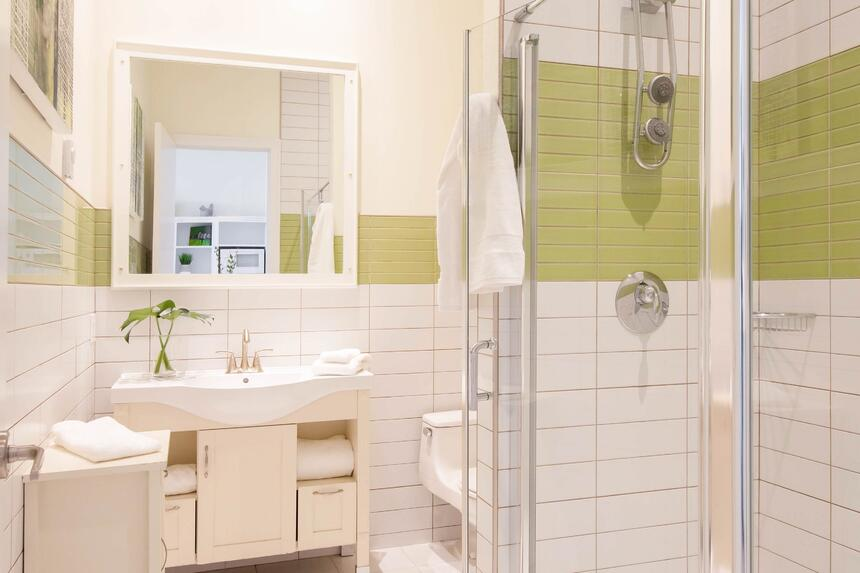 bathroom with green and white tiled glass walk in shower
