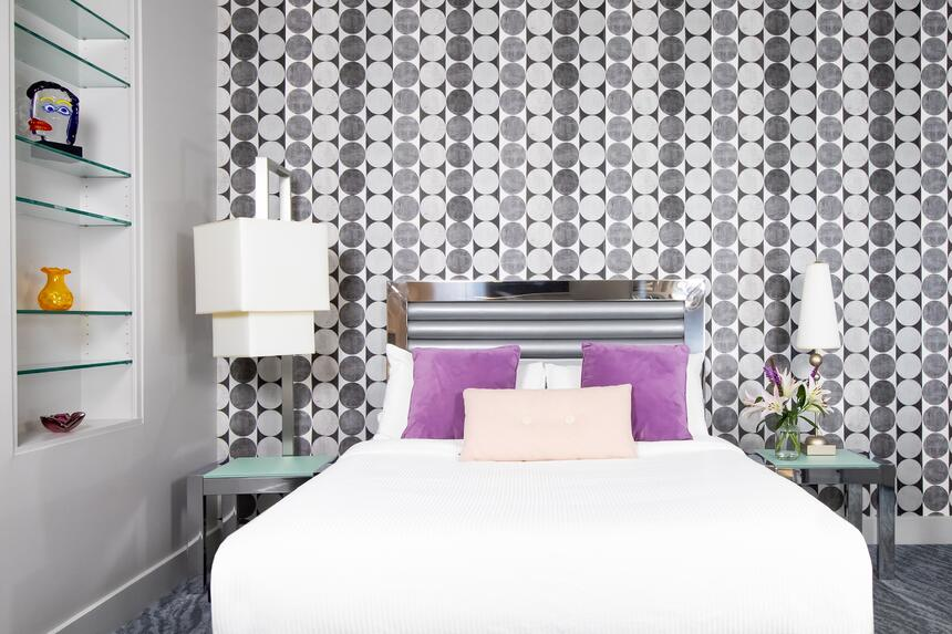queen bed with purple accent pillows in front of decorative wall