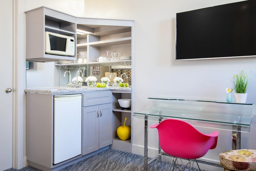 pink chair and glass desk near kitchenette with microwave and fr