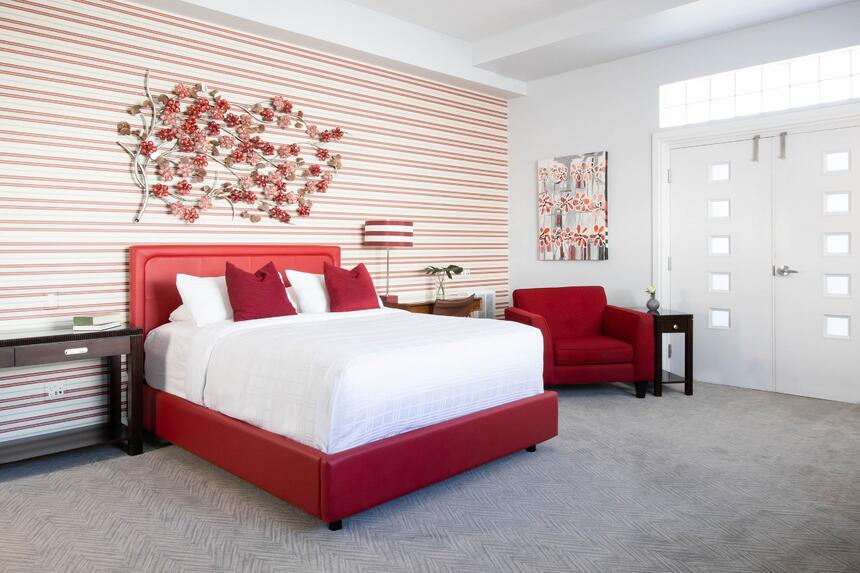 queen bed suite with balcony doors in view and red metal flowers