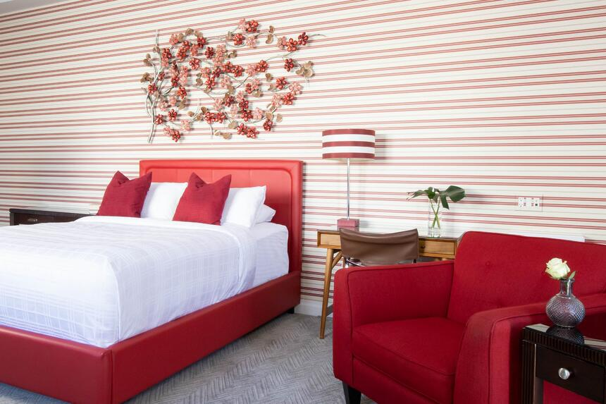 queen bed with red chair beside and red and white striped walls