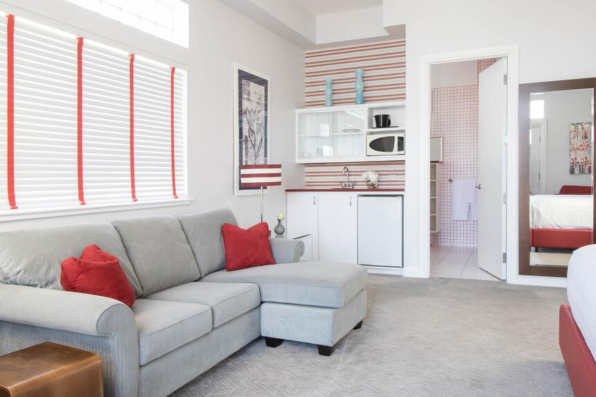 couch with kitchenette in view with fridge, microwave and sink