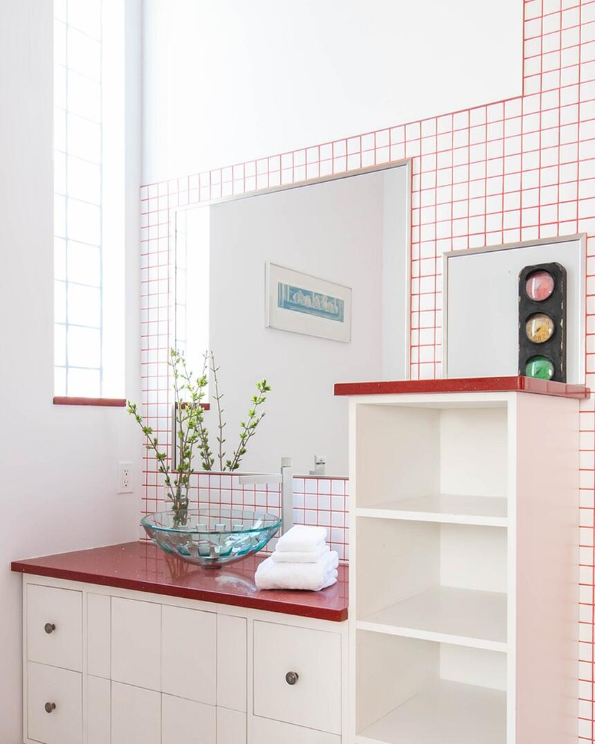 bathroom with red countertop and glass bowl sink