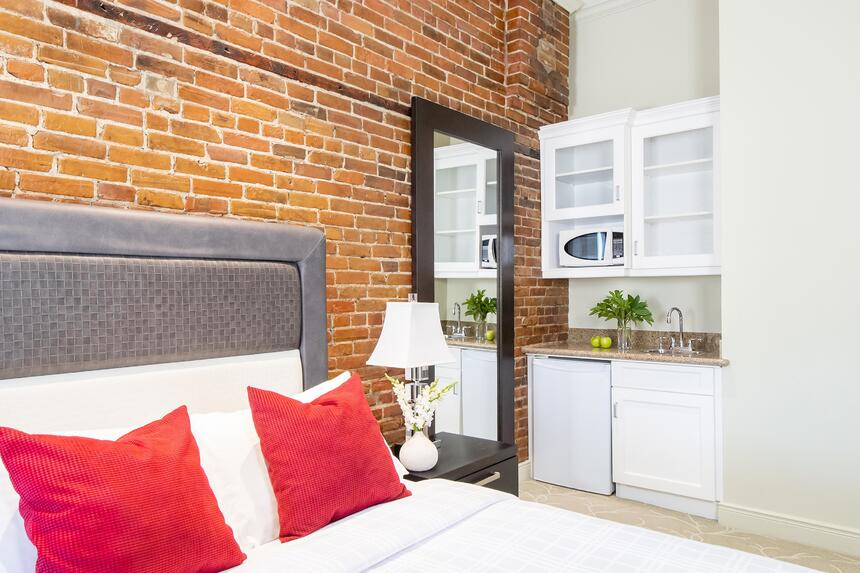 kitchenette in midtown with full length mirror beside and brick