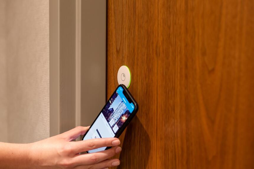 person unlocking door with phone