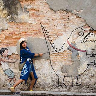 penang mural of little boy with pet dinosaur