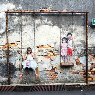 A penang mural of brother & sister on a swing
