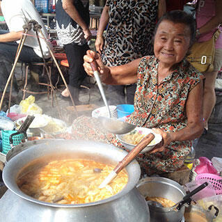 An old lady serving curry in penang