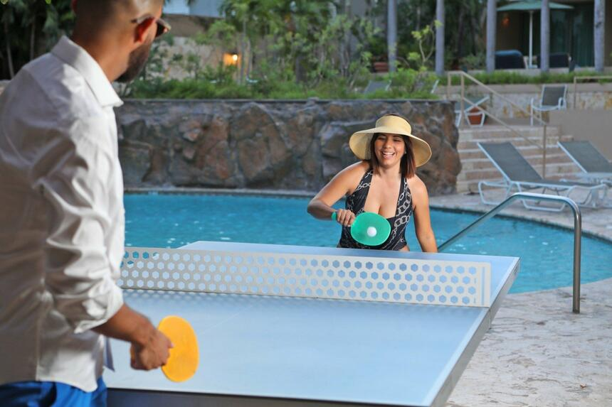 couple playing table tennis near pool