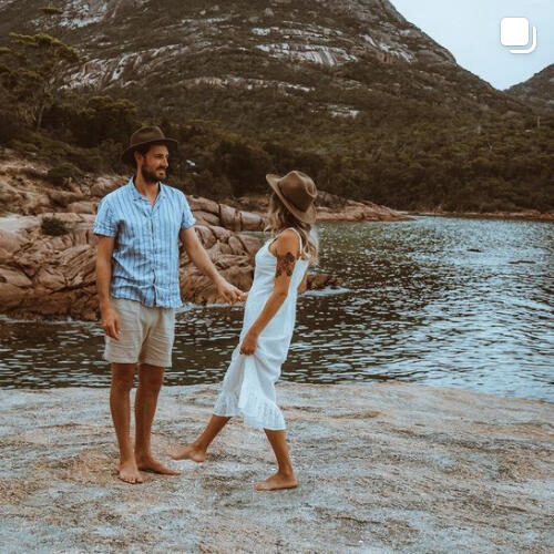 A couple standing on a rock near the bay at Freycinet Lodge