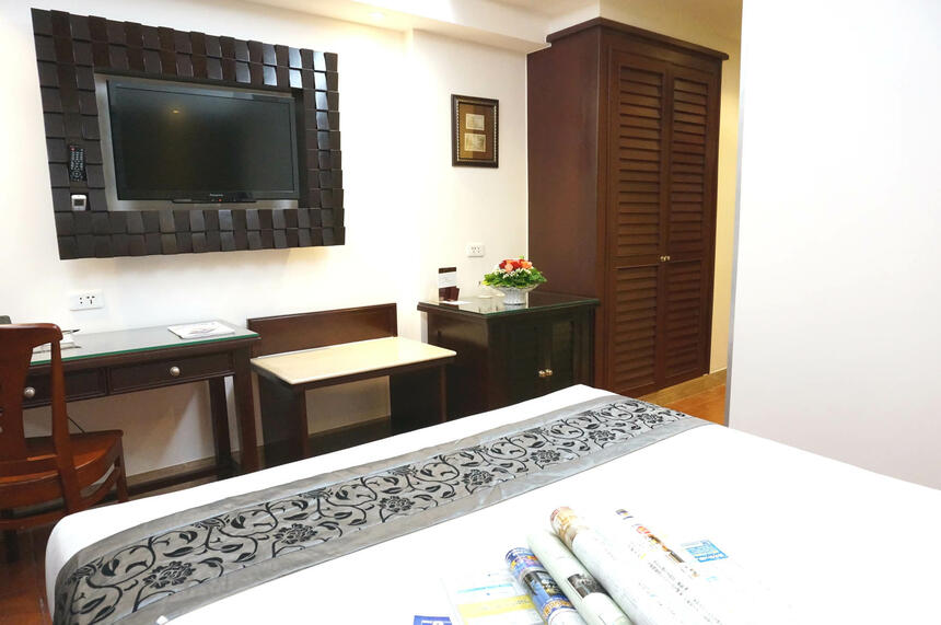 Deluxe Bedroom with a TV and furniture at Empress Hotel