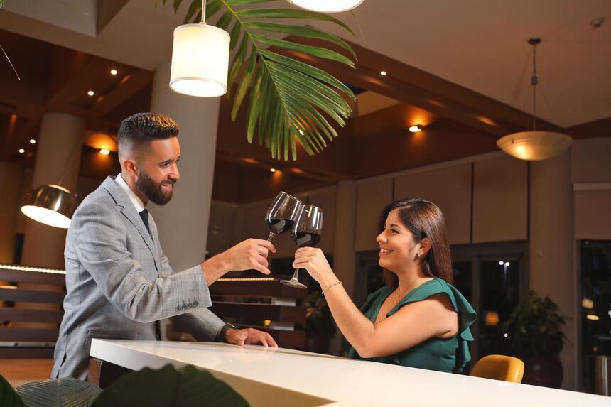 couple cheersing wine glasses in restaurant