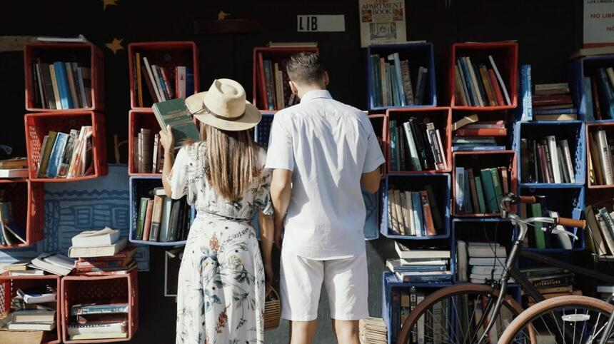 couple lookin through old books in outdoor store