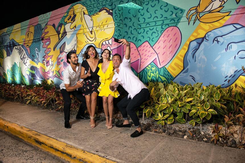 group taking selfie near graffiti art