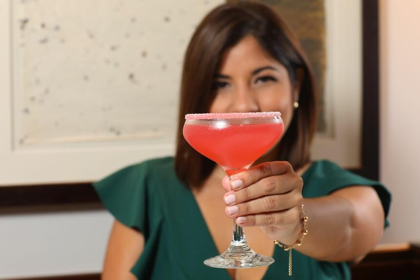 woman showing off cocktail drink