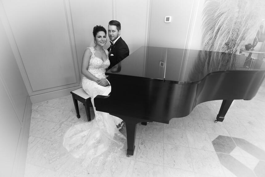 bride and groom near black piano at The Inn of Waterloo