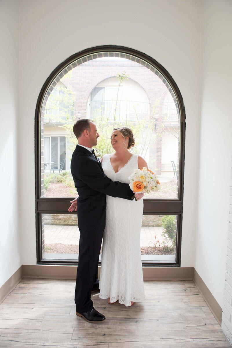 happy bride and groom near window at The Inn of Waterloo