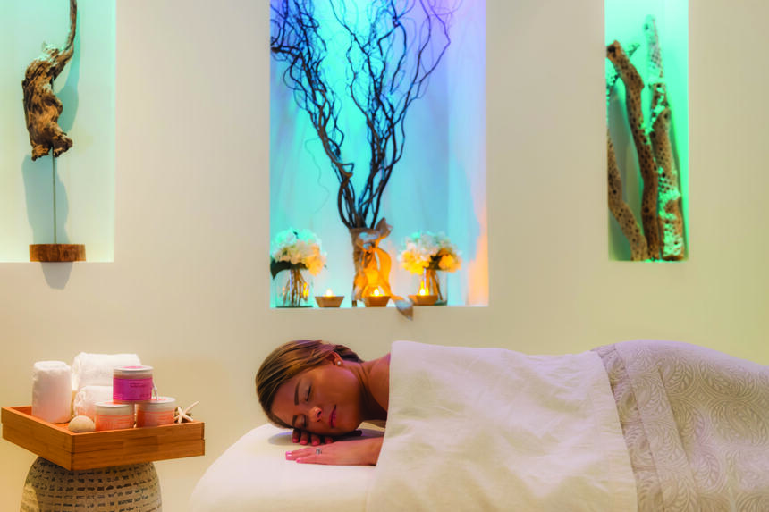A woman lying on spa bed in Drift spa at Windsong Resort On The Reef