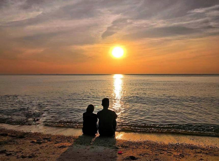 Couple enjoy sunset view at Blue Lagoon Beach Port Dickson