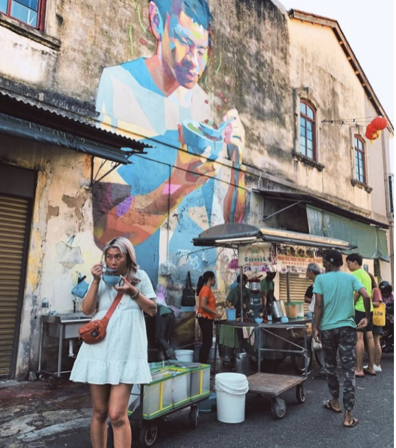 penang local street food in front of a mural