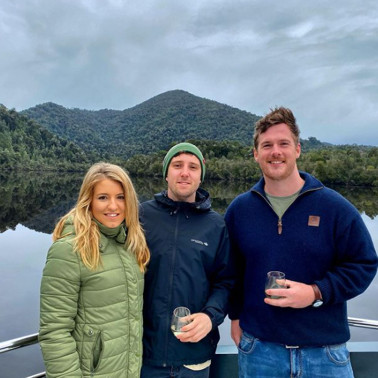 Three people standing near the river at Gordon River Cruises