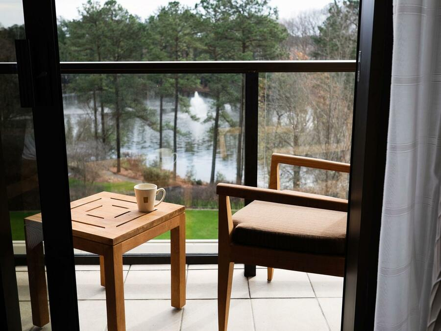 seats and table on the balcony of hotel overlooking lake