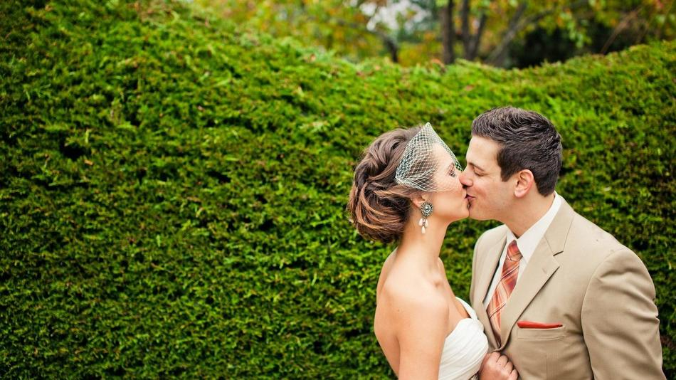 Bride and groom kissing in a garden