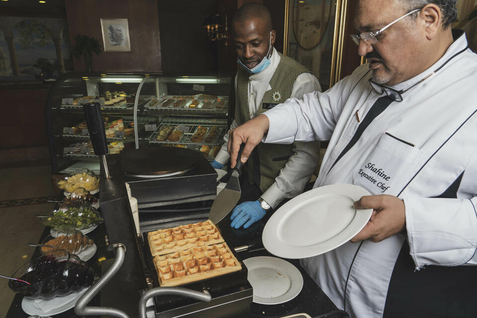 A man taking a waffle from a waffle toaster