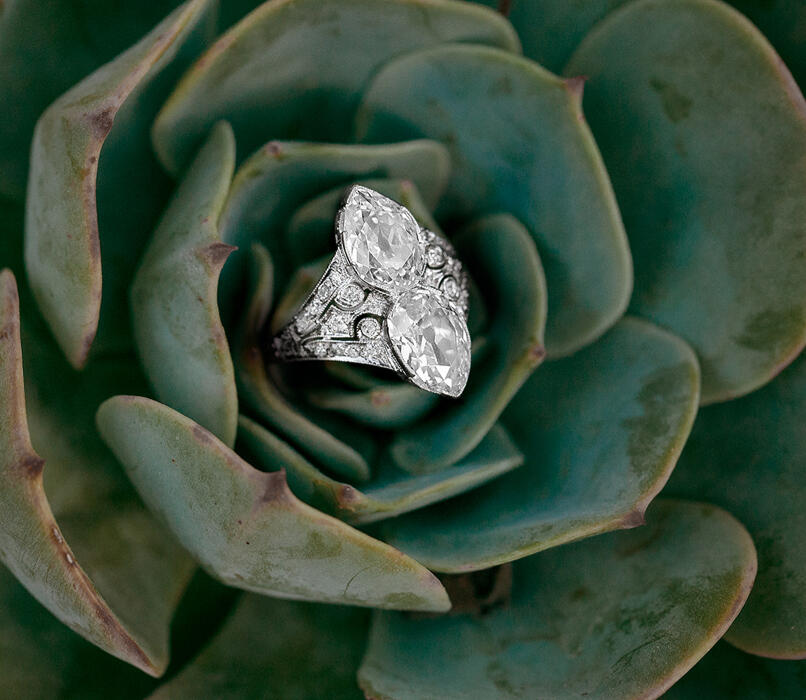 A silver ring with diamonds inside a green flower
