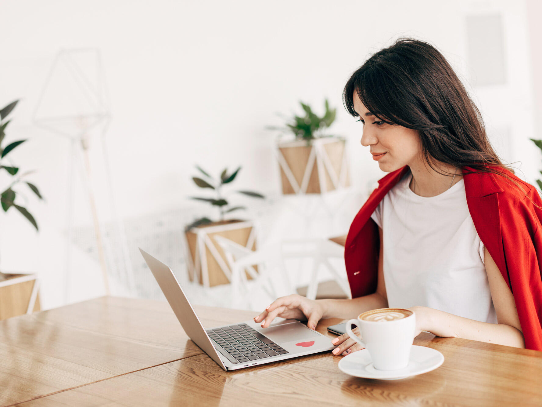 A lady working on the laptop while drinking coffee
