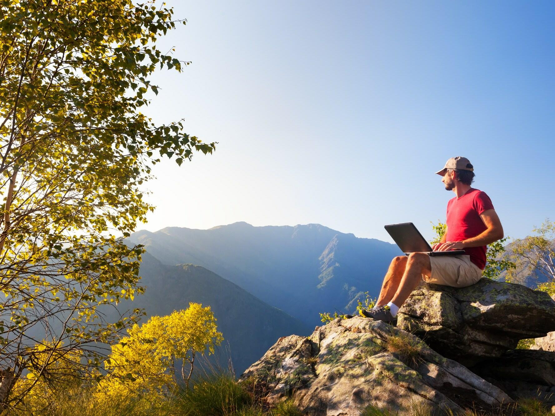 A man working on the laptop while sitting on top of a rock, enjoying the view