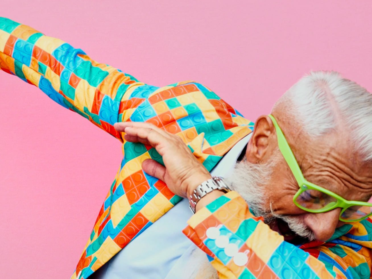 An old man who is wearing a colorful outfit doing the dab