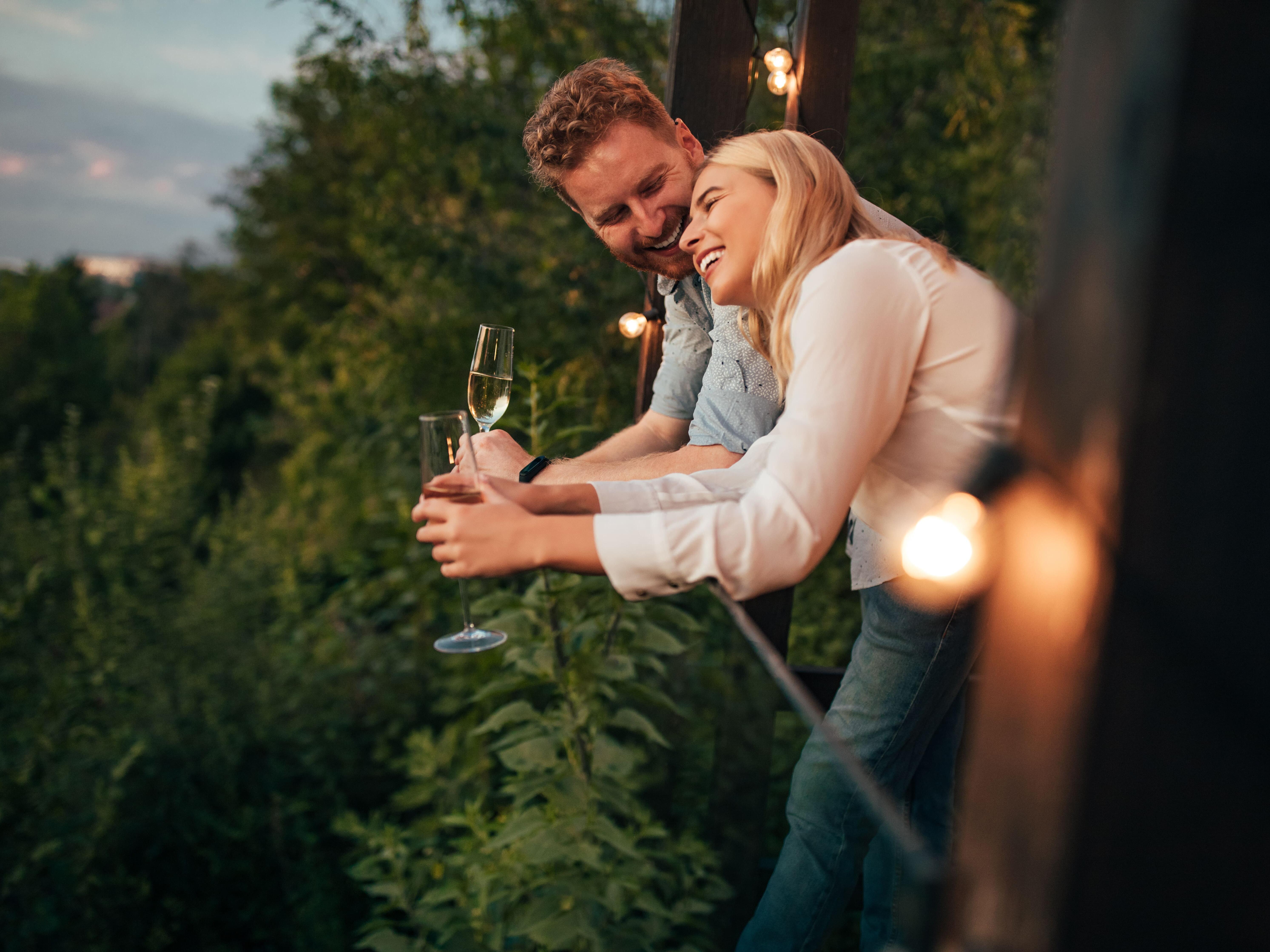 Happy couple on a balcony enjoying the tree tops