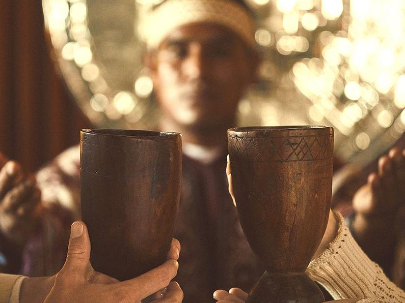 Two people holding two cups closely that's made of wood