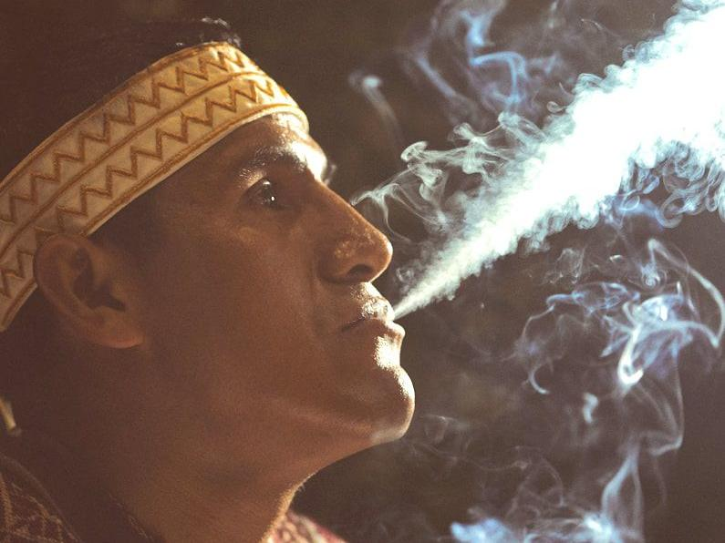 A person in a traditional outfit blowing smoke from his mouth