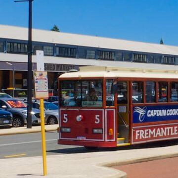 Red bus parked at a bus station near Be Fremantle