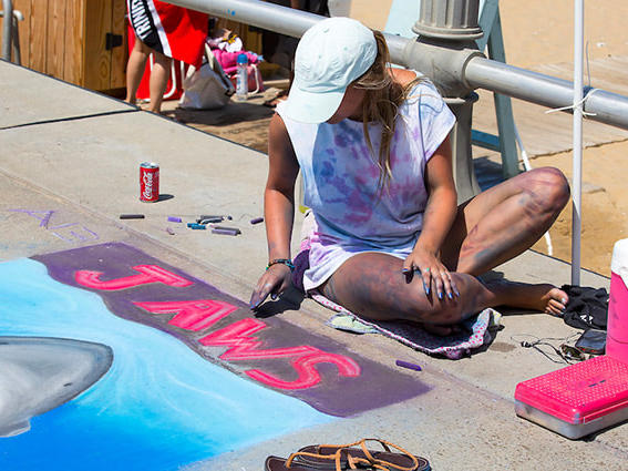 girl-drawing-chalk-mural-of-jaws-movie-poster-on-virginia-beach-boardwalk