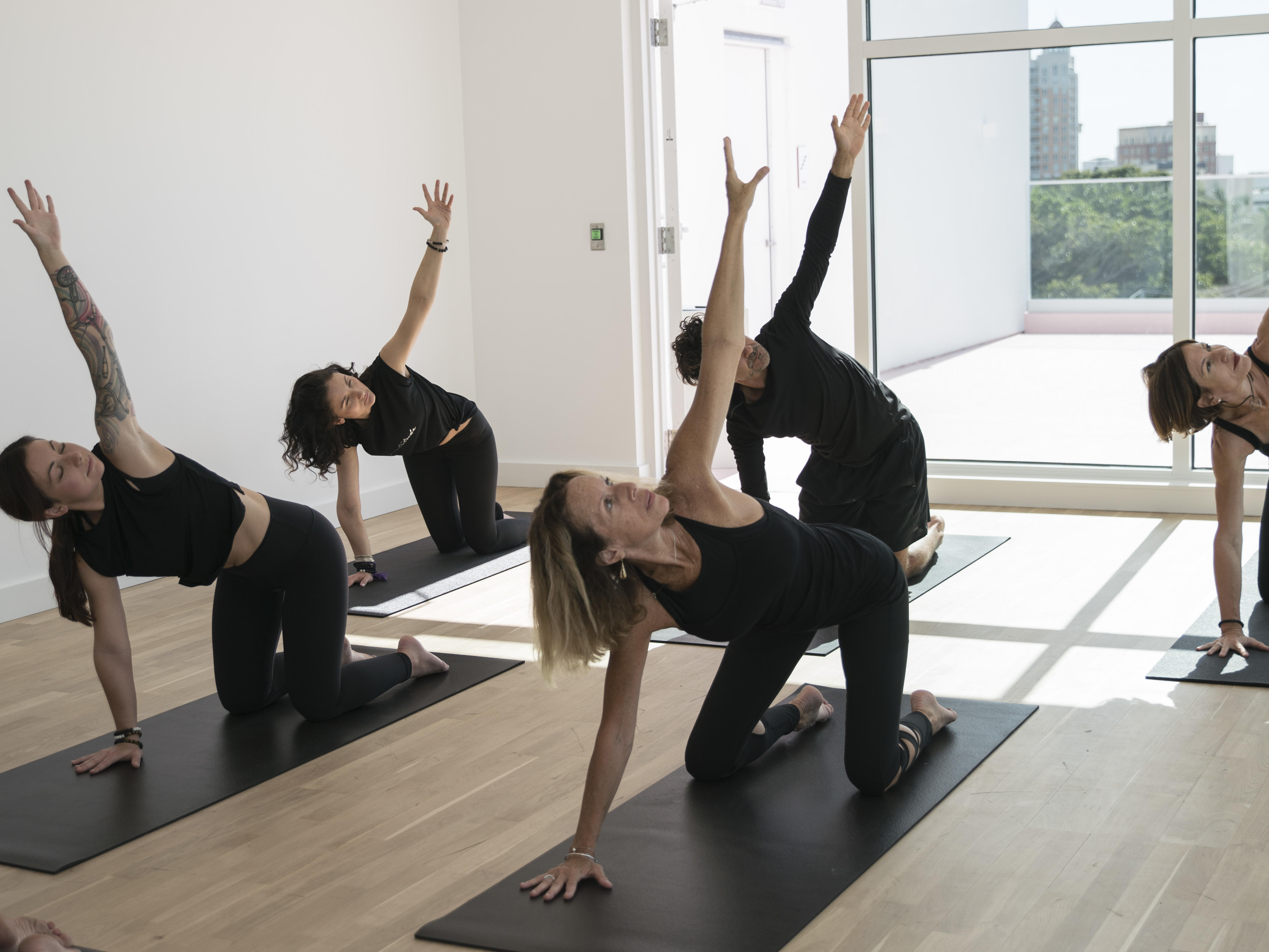 group of people practicing yoga on mats in studio