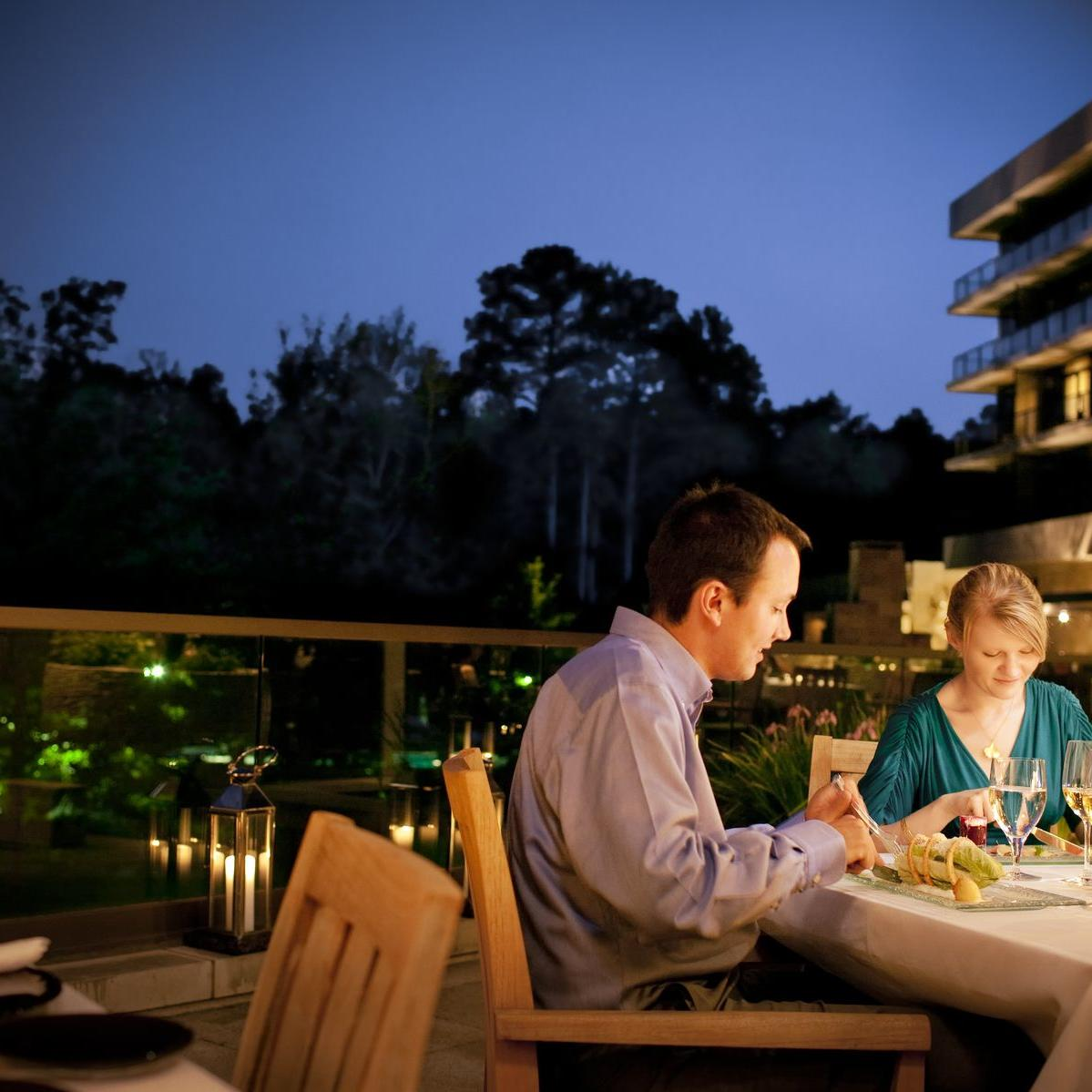 couple eating dinner outside with wine glasses