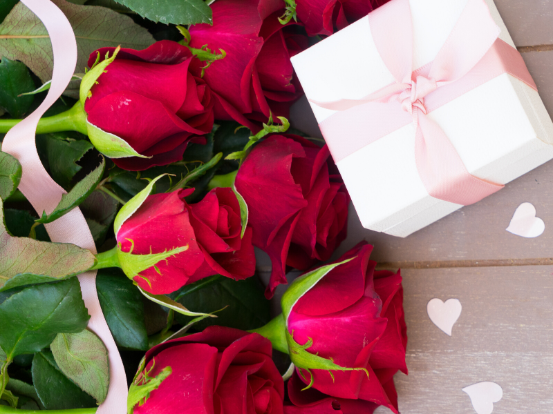 roses with gift boxes and pink ribbon